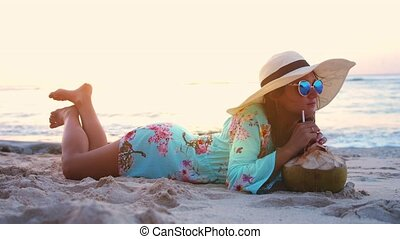 Young tourist pretty woman in sunglasses and the hat lying on tropical paradise sandy beach and drinks coconut juice during beautiful sunset. slow motion.