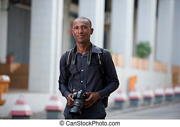 young tourist walking in town with camera