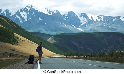 young tourist with a backpack and sunglasses hitchhiking on a mountain road 50 fps
