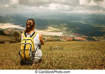 Young tourist with backpack relaxing on top of the mountain...