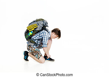 Young tourist with backpack ties up shoelaces on white background