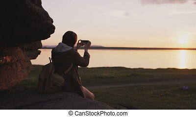 Young tourist woman backpacker photographing landscape on her smartphone camera after hiking on rock at sunset