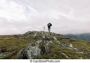 woman climbs to the binoculars on a hillside
