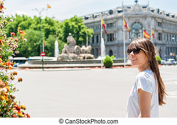 Young tourist woman in front Cibeles Fountain, one of the most famous monuments of architecture of Madrid located on the Cibeles square in the Centre of Madrid, Spain