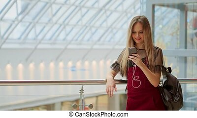 Young tourist woman in hat, with backpack stands at airport and uses smartphone.Hipster girl checks email, chatting, blogging, browsing internet.Online marketing, education. Distance work, e-learning.