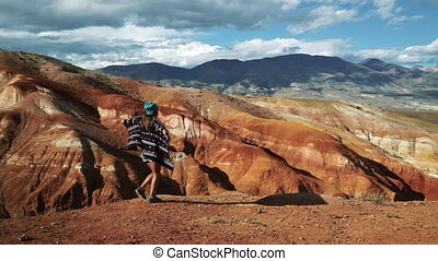 young tourist woman in shorts and a shirt walks along the edge of the huge beautiful red canyon and wind coats 50 fps