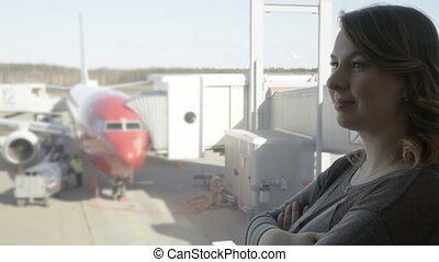 Young tourist woman in the airport, looking through the window at plane