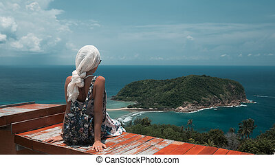 Young tourist woman is sitting on a viewpoint of beautiful sea bay landscape