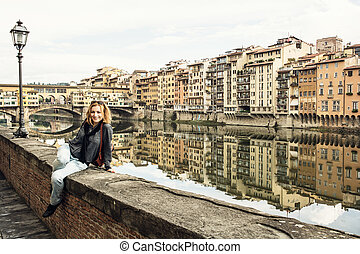 Young tourist woman is sitting on the wall in front of the Ponte Vecchio in Florence city