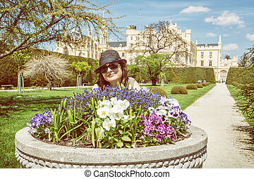 Young tourist woman posing with flowerbed and Lednice castle, beauty filter