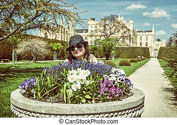 Young tourist woman posing with flowerbed and Lednice castle in background, retro filter