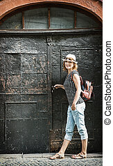 Young tourist woman posing with old door