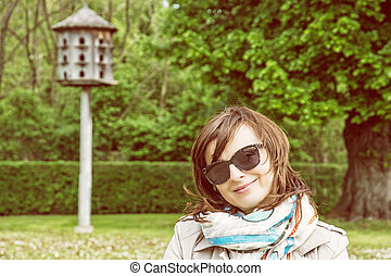 Young tourist woman posing with wooden dovecote, yellow photo filter
