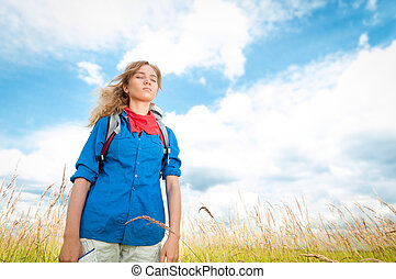 Young tourist woman relaxing in summer field.