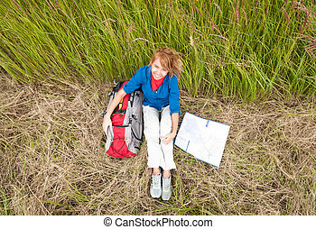 Young tourist woman resting in field.