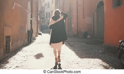 Young tourist woman walking up the small street in sunny. Stylish girl spending vacation in Europe, exploring the old town. Woman enjoying the new city.