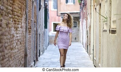 Young tourist woman walking up the small street in sunny day. Girl spending vacation in Europe, exploring old town.