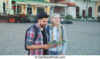 Young tourists couple finding necessary destination on map and admiring surroundings. They standing on city square.