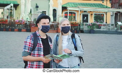 Young tourists couple in protective masks using map on ...