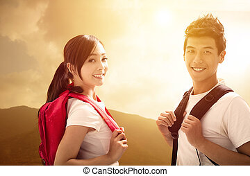 Young tourists couple with backpacks enjoy hiking