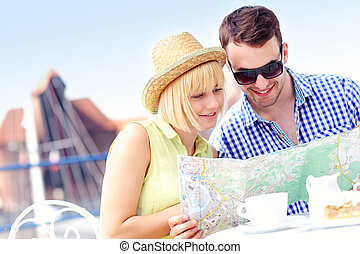 Young tourists with a map in a cafe