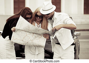 Young tourists with a road map at the retro car