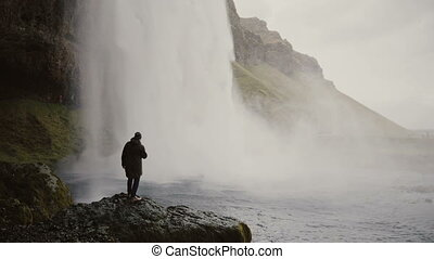 Young tourists with action camera near the Gljufrabui waterfall in Iceland. Man looking on famous sight of North nature.
