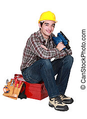 young tradesman sitting on toolbox holding sander machine