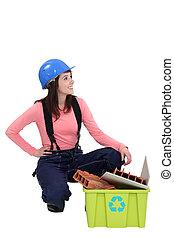 Young tradeswoman squatting beside a recycling bin