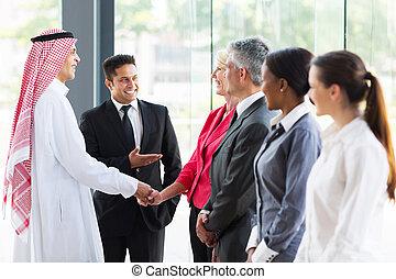 young translator introducing Arabian businessman to business partners