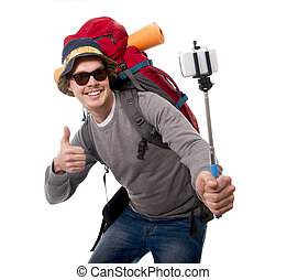 young traveler backpacker taking selfie photo with stick carrying backpack ready for adventure