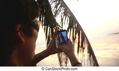 Young traveler in sunglasses sits on a palm tree on a background of beautiful sunset takes picture with nobile phone, slow motion. 1920x1080