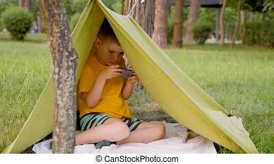 Young traveler in tent playing video game. Traveling concept...