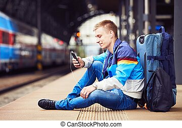 Young traveler is waiting at the railway station