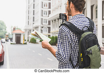 Young traveler photographing sightseeing in town