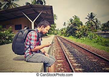 Young traveler with mobile phone in the railway