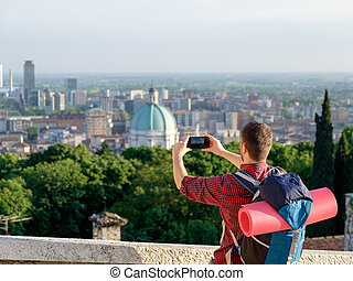 Young traveler standing and taking a picture of a city landscape