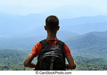 Young traveler with backpack on mountains background