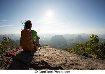 young traveler with backpack sit on the mountain peak rock...