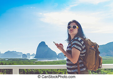 Young traveler woman find way direction with map on mobile phone at beautiful of nature at top of mountain and sea view,travel wanderlust backpacker concept