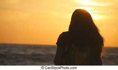 Young traveler woman standing on ocean shore and looking at sunrise. Young female tourist with backpack enjoying view of sea beach at sunset. Girl hiker on travel or summer vacation. Rear back view