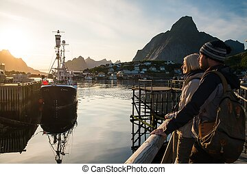Young travelers couple looking at sunset in Reine village,...