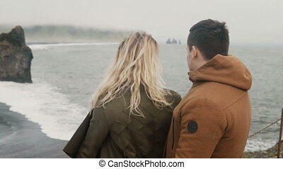 Young traveling couple on black beach in Iceland looking on...