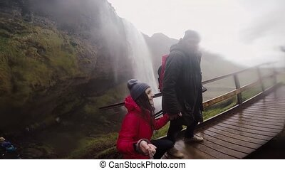 Young traveling couple walking near powerful Seljalandsfoss waterfall in Iceland together. Slow motion on action camera.