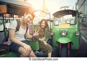 young traveling man and woman sitting on tuk tuk domestic...