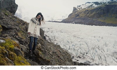 Young traveling woman walking through the rocks in the mountains, exploring the Vatnajokull glaciers lagoon in Iceland.