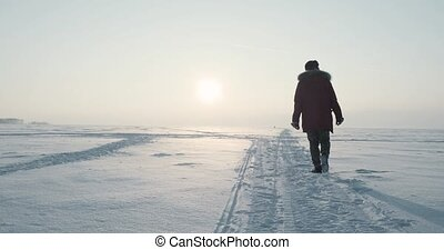 Young traveller goes through a blizzard at beautiful sunset....