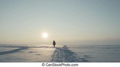 Young traveller goes through a blizzard at beautiful sunset. Polar expedition