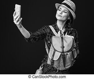 young traveller woman taking selfie with smartphone