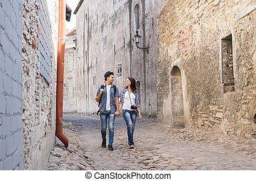 Young travelling couple having a walk on an old street with tile road